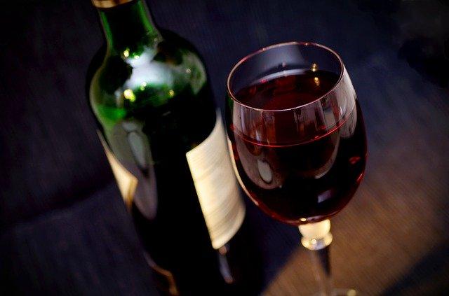 Rotwein im Glas und Flasche
